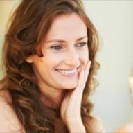 Portrait of happy woman looking herself in mirror